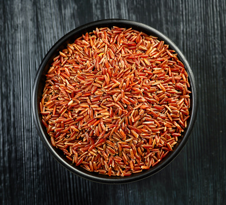 brown rice: bowl of red wild rice on black wooden table, top view Stock Photo