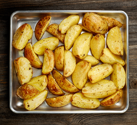 wedges: roasted potatoes with spices on oven pan, top view Stock Photo
