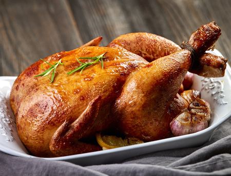 baked chicken: roasted chicken with vegetables on wooden table