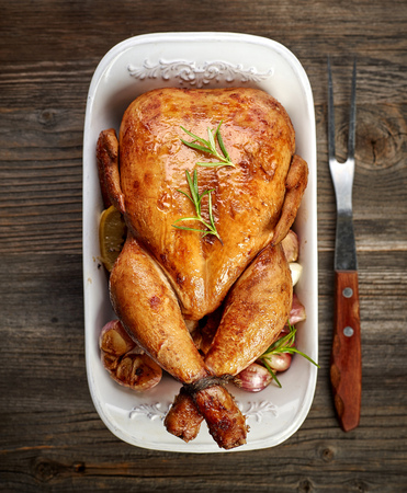 meat dish: roasted chicken with vegetables on wooden table, top view Stock Photo