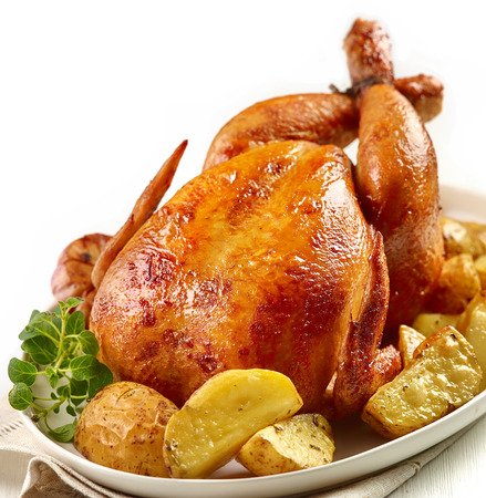 whole chicken: roasted chicken with potatoes on white plate
