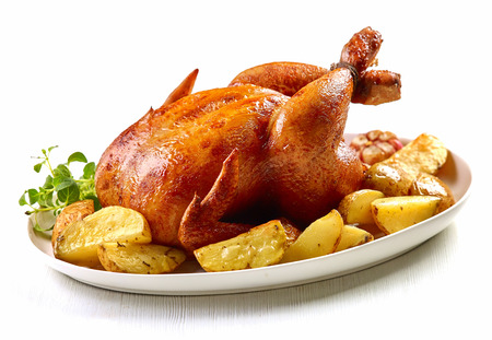 baked chicken: roasted chicken and potatoes on white plate