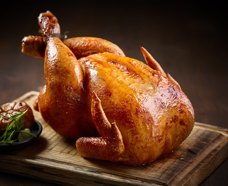 roasted chicken on wooden cutting board Standard-Bild