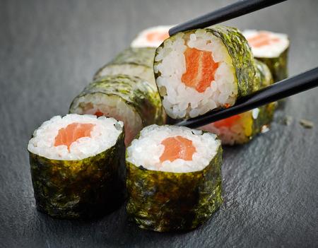 sake maki: salmon sushi on black plate