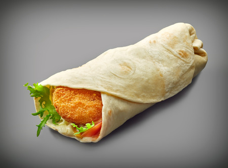 gray background: Wrap with fried chicken and vegetables on a dark gray background