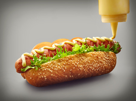 Hot dog with pouring mayonnaise on dark gray background Stock fotó