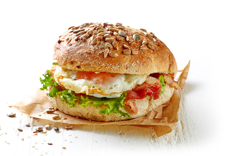 bacon and eggs: healthy sandwich on white wooden table