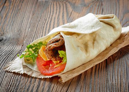 bocadillo: envolver con carne y verduras en la mesa de madera