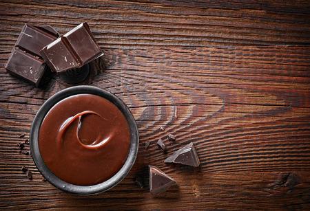 merienda: crema de chocolate y trozos de chocolate en la mesa de madera, vista desde arriba