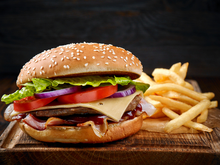 fresh tasty burger and french fries on wooden cutting board