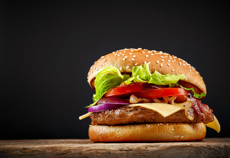 fresh tasty burger on wooden table Imagens
