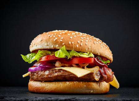 hamburguesa: sabrosa hamburguesa fresca sobre fondo oscuro