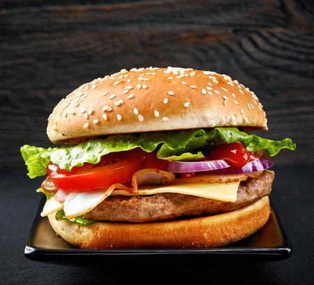 burgers: fresh tasty burger on black plate Stock Photo