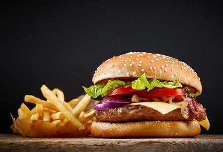 pasteleria francesa: sabrosas hamburguesas y patatas fritas frescas en la mesa de madera