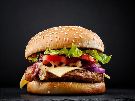 lekkere verse hamburger op zwarte achtergrond Stockfoto