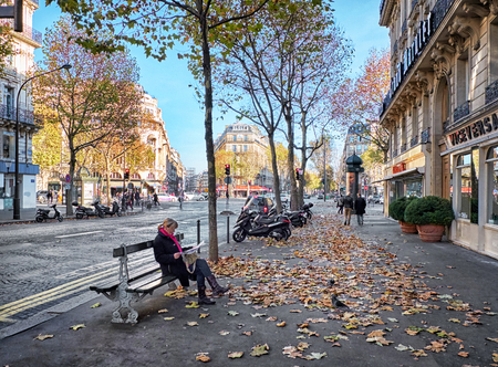 Paris, France-November 15, 2015: Boulevard Haussmann in Paris, France. It is one of the wide tree-lined boulevards created in Paris by Napoleon III, it is mostly lined with apartment blocks.Toned image