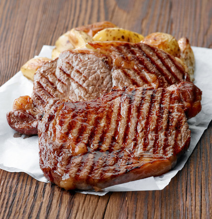 new york strip: grilled beef steak on wooden table
