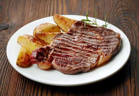 new york strip: grilled beef steak and potatoes on white plate