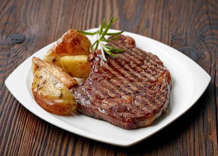 나무 테이블에 구운 쇠고기 스테이크
