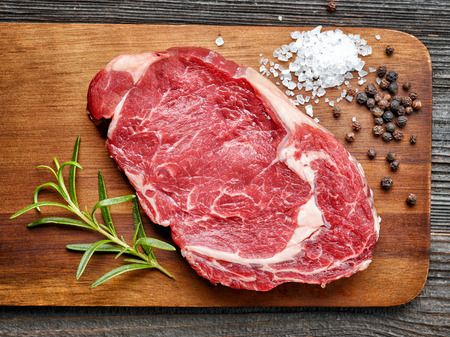 raw beef steak and spices on wooden cutting board, top view Standard-Bild
