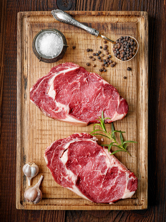 fresh raw beef steak on wooden cutting board, top view