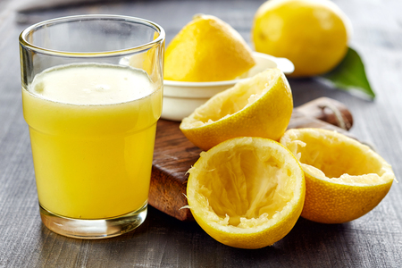 glass of lemon juice on wooden table Stock Photo