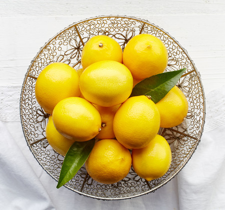 bowls: fresh natural lemons on white wooden table, top view