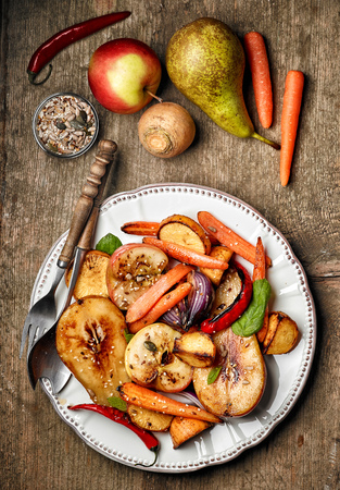 rutabaga: Plate of roasted fruits and vegetables on wooden table, top view