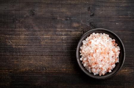 kom van roze Himalaya zout op donkere houten tafel, bovenaanzicht