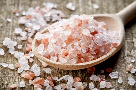 himalayan salt: spoon of pink himalayan salt on wooden table