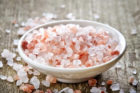 himalayan salt: bowl of pink himalayan salt on wooden table