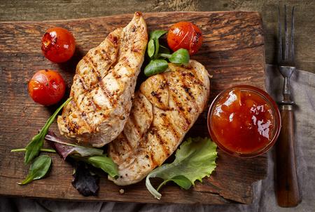 carne de pollo: filetes de pollo a la parrilla en la tabla de cortar madera