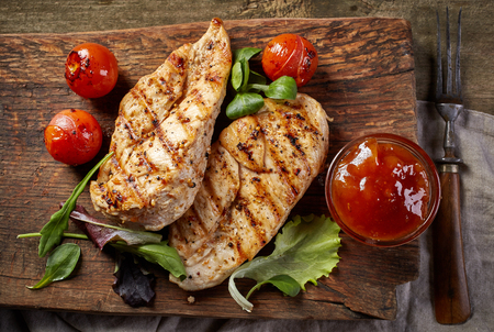grill chicken: grilled chicken fillets on wooden cutting board