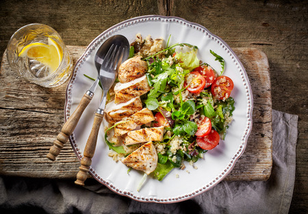 white plate: Quinoa and vegetable salad and grilled chicken fillet on white plate, top view