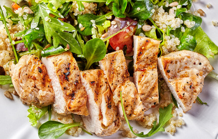 Quinoa and vegetable salad with grilled chicken fillet, top view