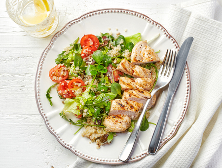 Quinoa and vegetable salad and grilled chicken fillet on white plate, top view Stock fotó - 50860914