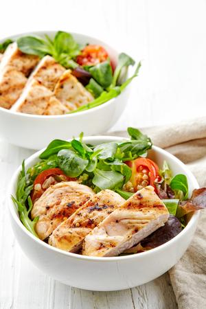pollo a la brasa: dos platos de ensalada de vegetales con filete de pollo a la parrilla