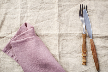 servilleta: linen napkin background with fork and knife, top view