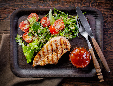Quinoa and vegetable salad and grilled chicken fillet on dark wooden plate, top view Фото со стока