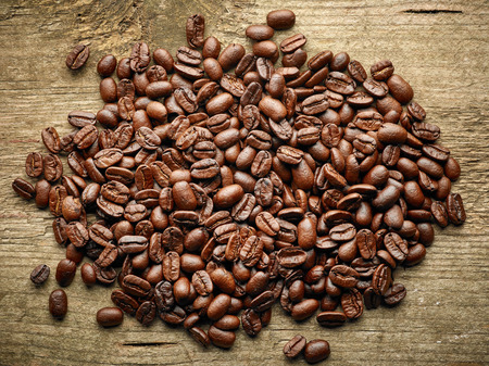 grano de cafe: Heap of Coffee beans on wooden table, top view Foto de archivo