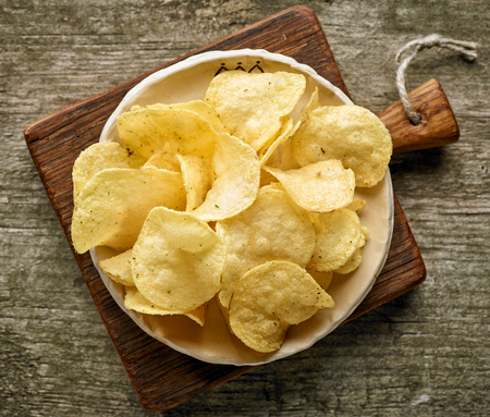 potatoes: potato chips on wooden table, top view