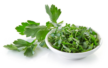 isolated on green: bowl of chopped parsley leaves isolated on white background