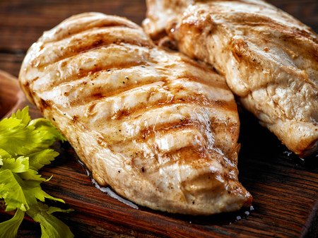 Grilled chicken fillets on wooden cutting board Stockfoto