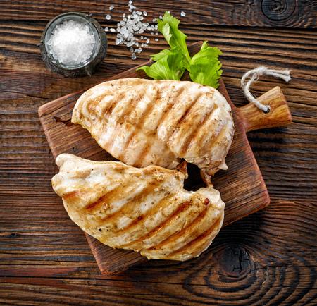 senos: filetes de pollo a la parrilla en la tabla de cortar de madera, vista desde arriba Foto de archivo