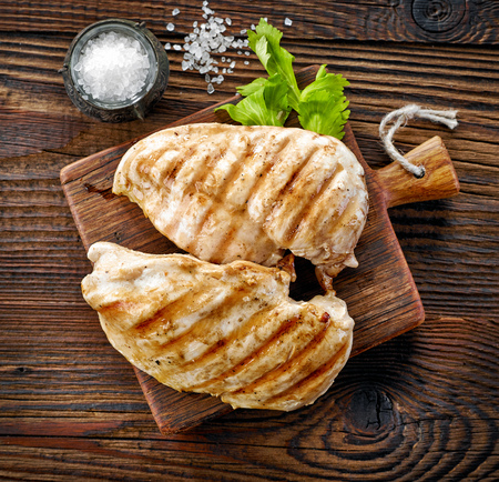 grilled chicken fillets on wooden cutting board, top view Stockfoto