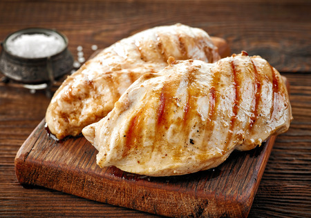 Grilled chicken fillet on wooden cutting board