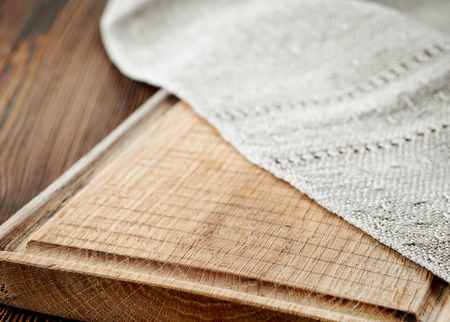 empty table: closeup of wooden cutting board and linen napkin