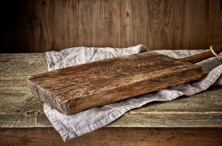 Cooking background with old wooden cutting board and linen kitchen towel