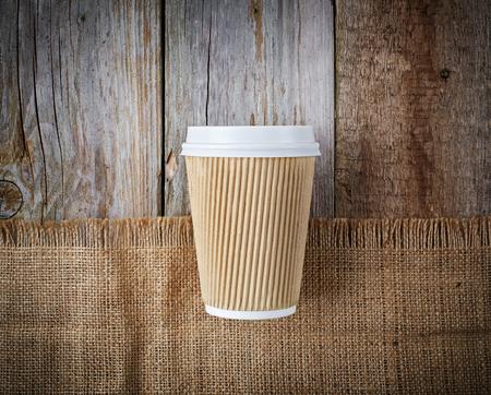 carta togliere tazza di caffè su fondo in legno e biancheria