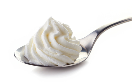 whipped cream in spoon isolated on white background